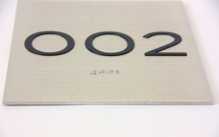 Tactile lettering and raster bead braille on brushed aluminum