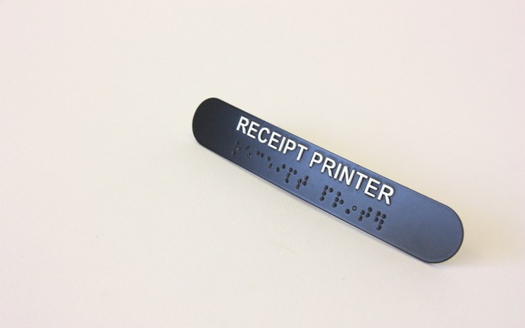 Raised tactile lettering and bead braille wayfinder/directional sign