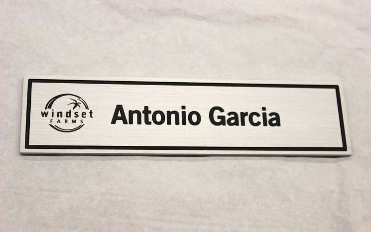 Brushed aluminum name plate with screen printed logo and rotary engraved, infilled border and name